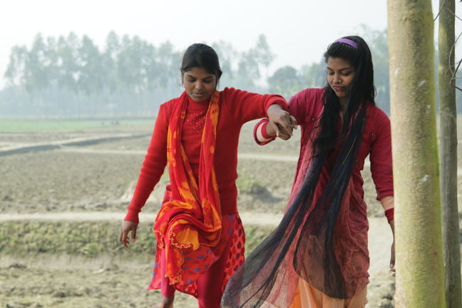 Two teenage girls walking. One girl is supporting the other