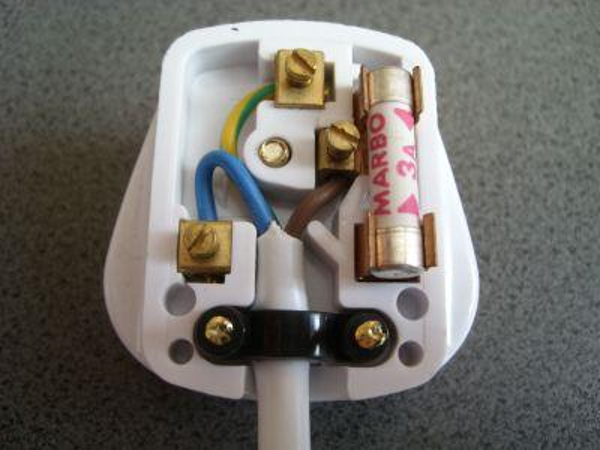 Electric plug opened (UK mains appliances) - with metal contacts where wires are screwed to the pins and a plastic outer shell