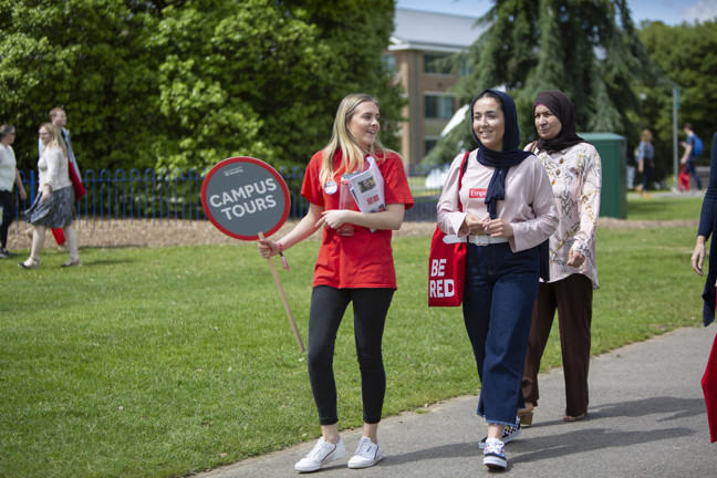 A University of Reading student ambassador is giving a campus tour to prospective students
