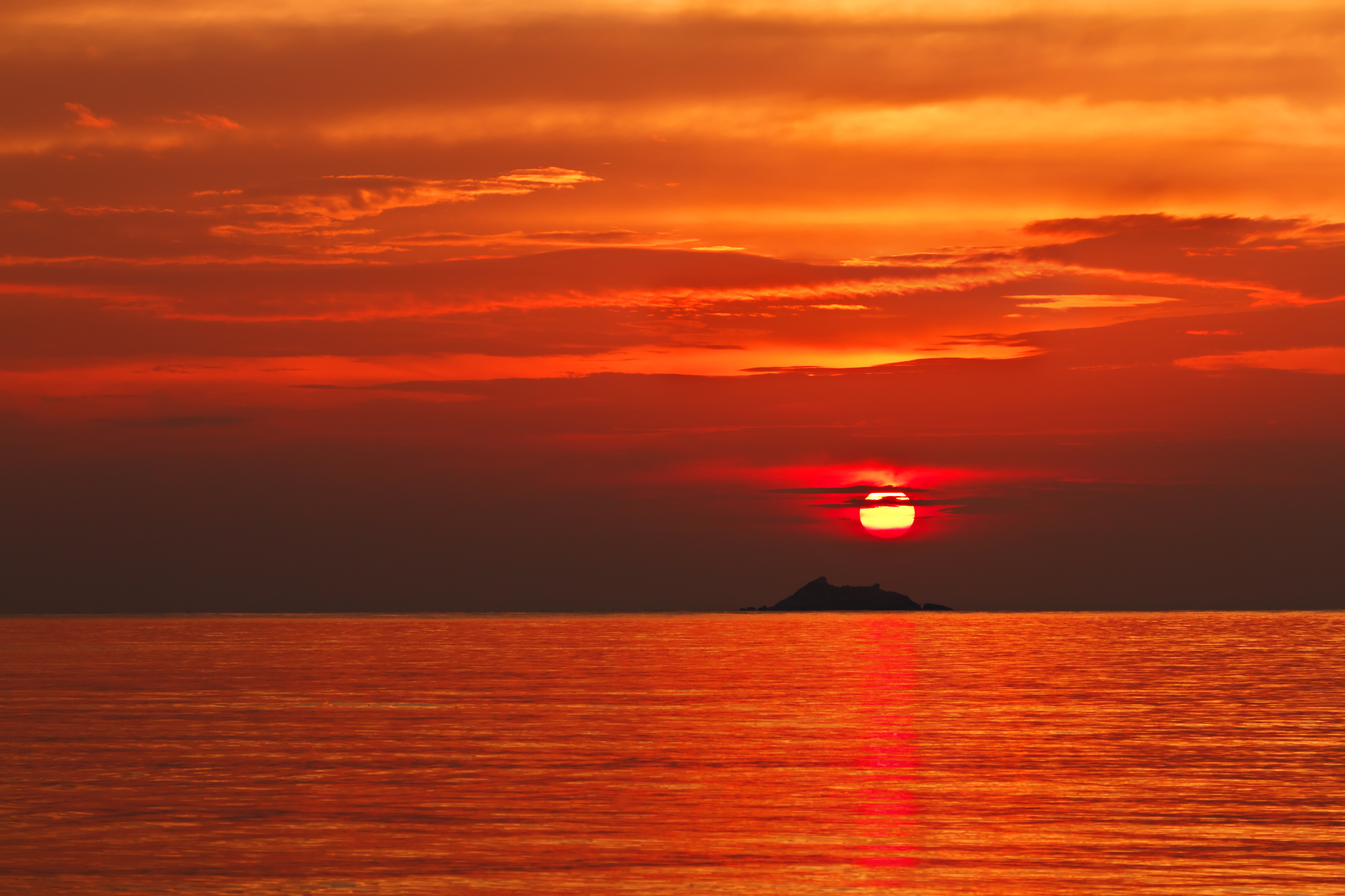Sun setting over the sea with an island in the distance. The sky is different shades of red