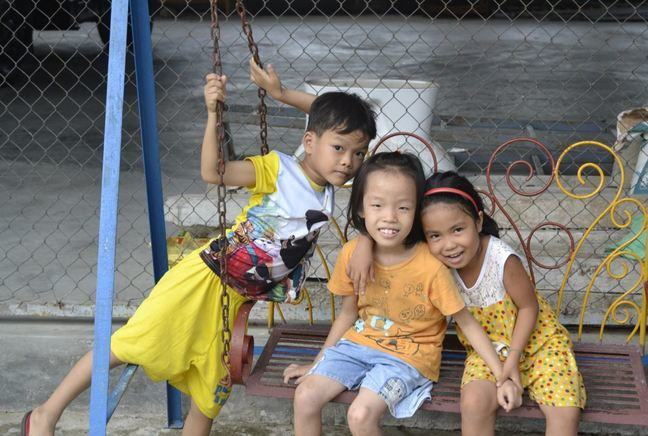 Two girls sitting side by side on a swing and smiling. A boy is standing next to the swing.