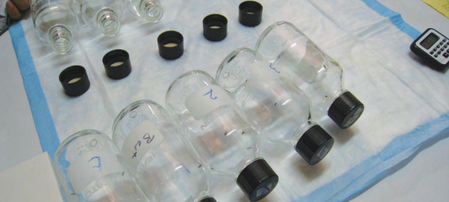 Figure 2: this image depicts the CDC bottle bioassay in action. Here you can see two rows of glass bottles laying on their side on a work surface, one with closed black lids and others with the lids removed. Mosquitoes are present inside the bottles with closed lids, and there is a timer device next to where the experiment is set up.