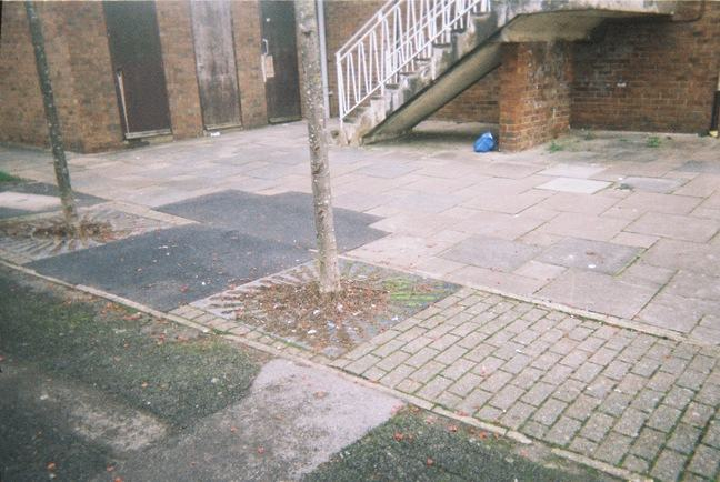 A slightly overexposed grainy photograph of an urban scene. In the foreground there are paving stones and patched up tarmac, and in the background we see a concrete stairway leading up to a red-brick building. Under stairs lies a blue polythene bag of rubbish.
