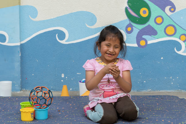 A girl is kneeling in front of a painted wall and laughing