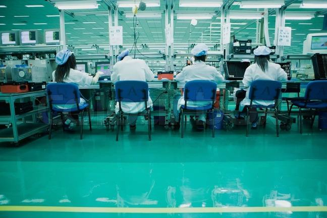 Workers at assembly line in a cell phone factory in China