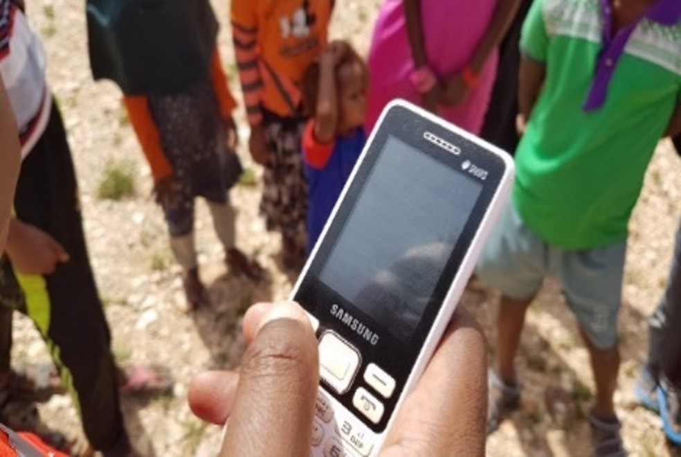 A person in front of children is holding a mobile phone to send community surveillance reports