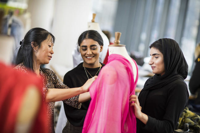 A lecturer with 2 students standing around a dressmakers mannequin draping fabric