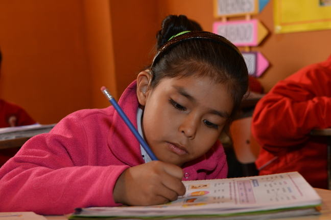 A girl with a hearing impairment is writing is her notebook.