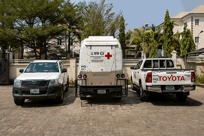 Three vehicles are stationed in a parking lot. These include two white pick-up trucks, one facing forward and one facing backward and a white mobile laboratory truck with a large red cross at its back