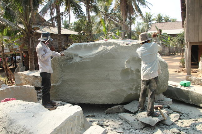 Two workers carving out a statue from sandstone