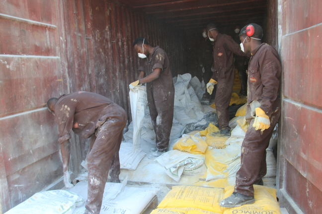 Workers handling broken bags with the lead powder mix