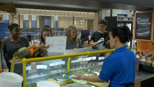 school lunch staff serves food to students