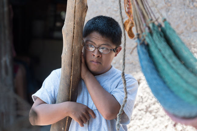 A teenager with Down syndrome is leaning against a wooden post.