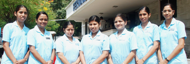 Seven Professional Midwifery Education and Training graduates standing in front of a clinic