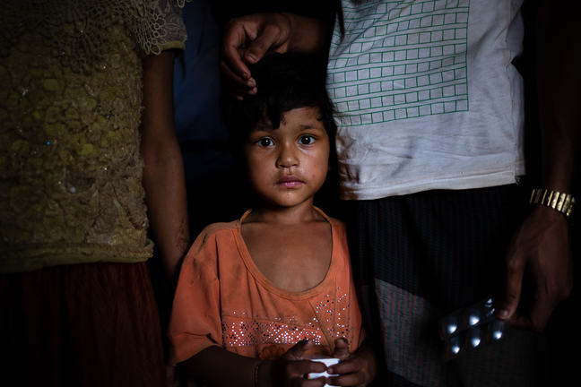 """""""A young girl wearing an orange shirt and holding a box of medicine is staring at the camera. Behind her are two adults, the one on her left is holding a packet of medicine."""""""
