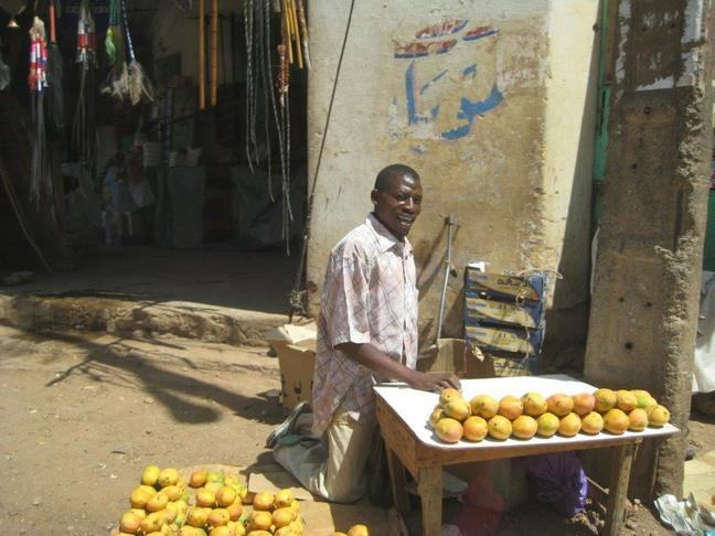 Man selling fruit in the street. His crutches are just behind him