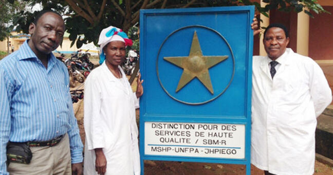 Three people standing in front of a medical services sign in Guinea