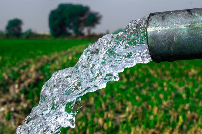 a photo of water pouring form a pipe, with an arable field in the background