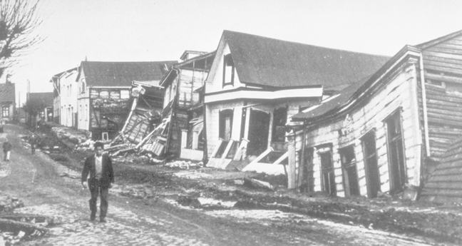 Showing damaged and collapsed houses on a street in Valdivia after the 1960 megaquake