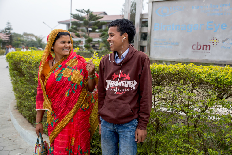 Mother and son looking at each other and smiling in Nepal. The son has just been fitted with a hearing aid
