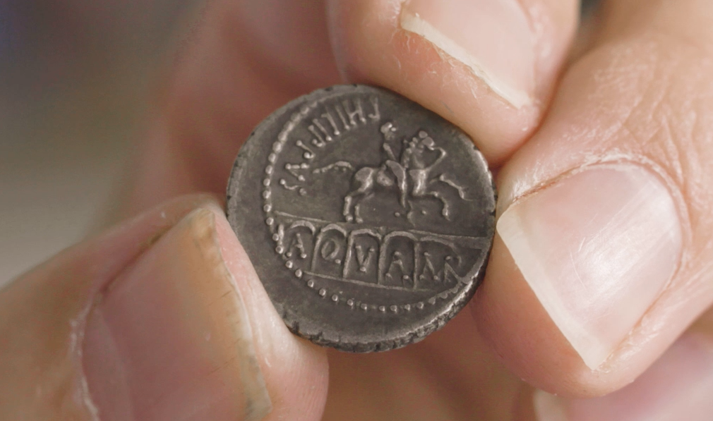 A copper coin showing a horse galloping across the top of an aqueduct