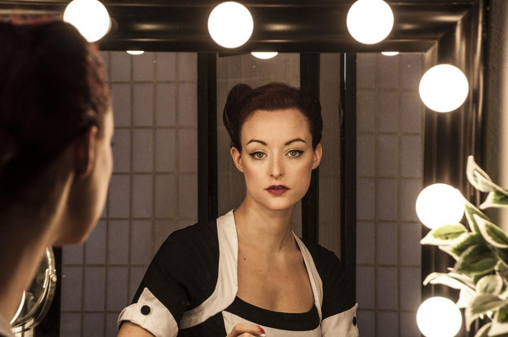 colour photo of the refelction of a woman in a dressing room mirror