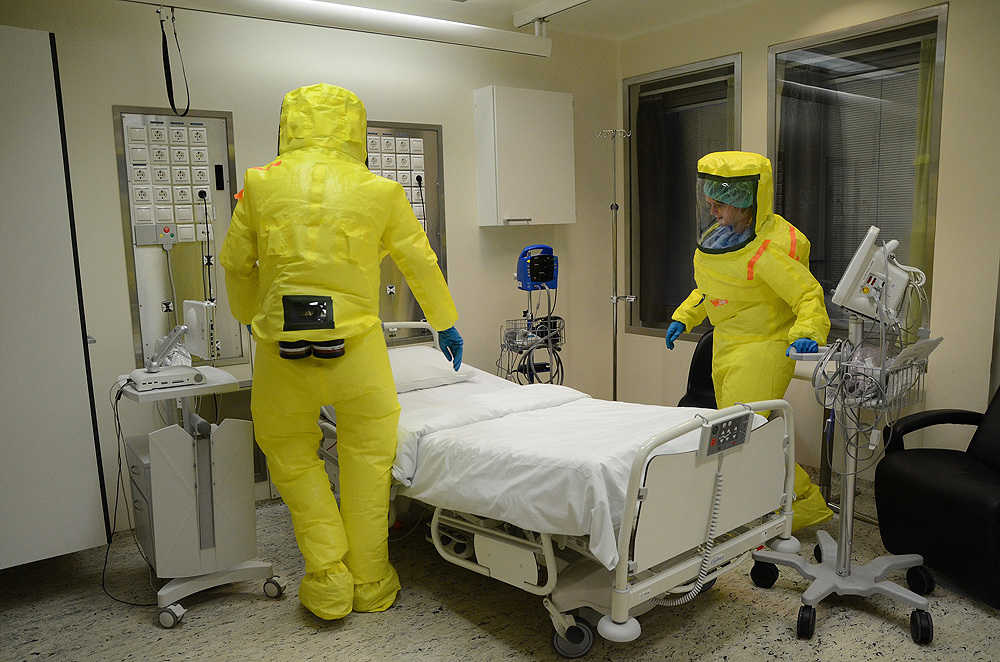 Inside a hospital room, two workers are dressed in protective gear for handling a patient with ebola virus