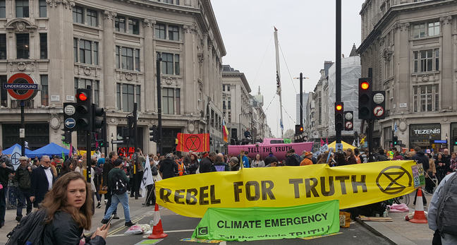 photo showing Extinction Rebellion protest in London, 2019. large yellow banner stating 'Rebel for truth'. Pink boat in the background with the text 'Tell the truth'