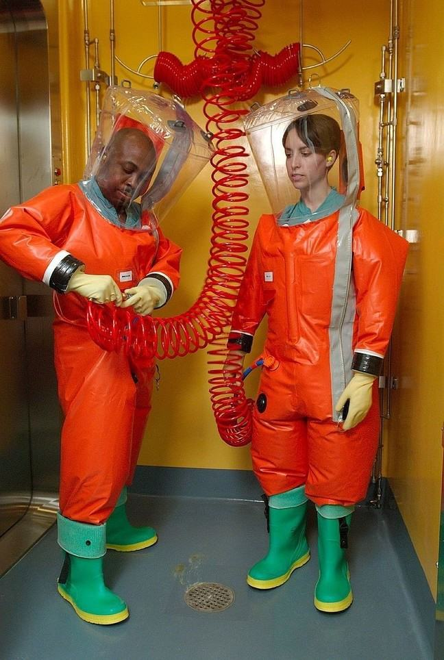 Two microbiologists putting on positive pressure biosafety suits which cover their entire body as well as a large clear cover over their head and wellington boots
