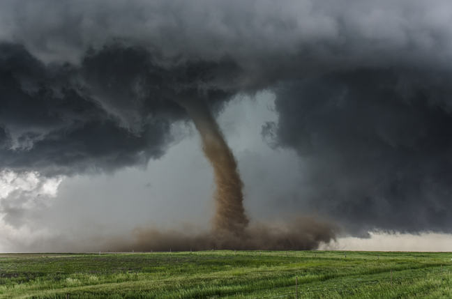 Tornado, centred in the image, coming from dark grey clouds and moving across green grass fields.