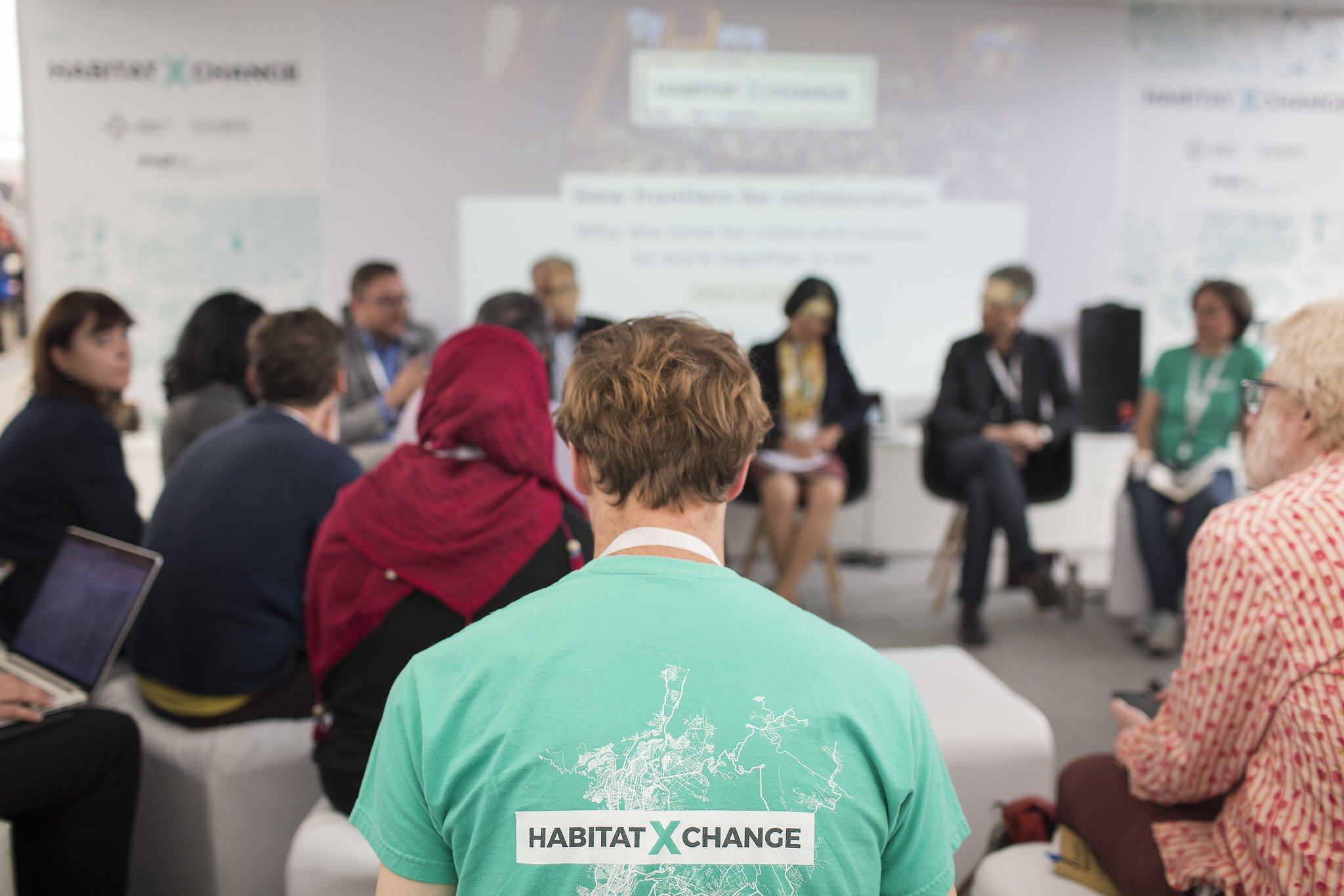 """Photograph of a man in a meeting wearing a green shirt with the label """"Habitat X Change"""""""
