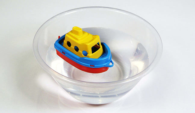 Toy boat floating on the surface in the middle of a bowl of water
