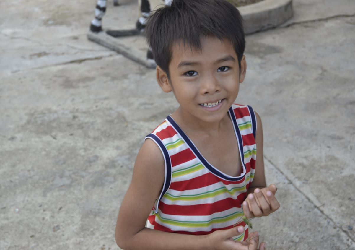 A boy is smiling at the camera.