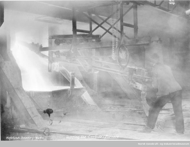 A worker is tapping a carbide furnace in a Norwegian smelter, dating from around 1925
