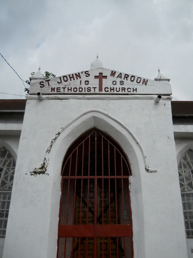White church front with a sign in red paint which reads, St John's Maroon Methodist Church, 1808