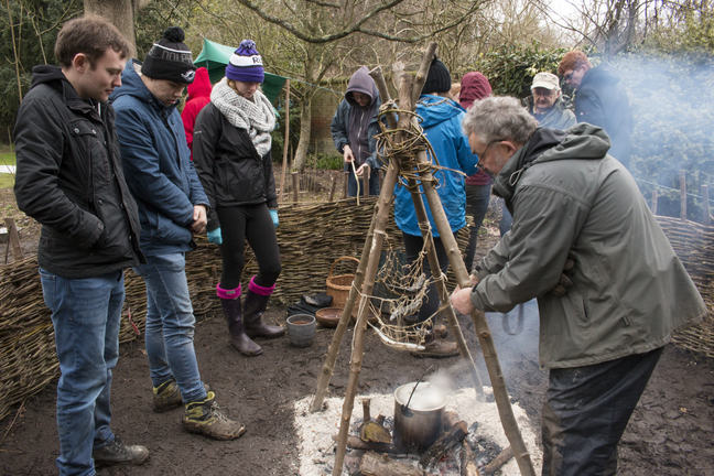 A photo of Martin Bell and a group of students conducting experiments on a hearth and chalk surface