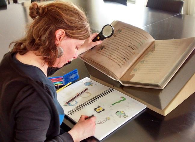 Figure 1 - Mags Harnett working from the facsimile copy of the Book of Kells.