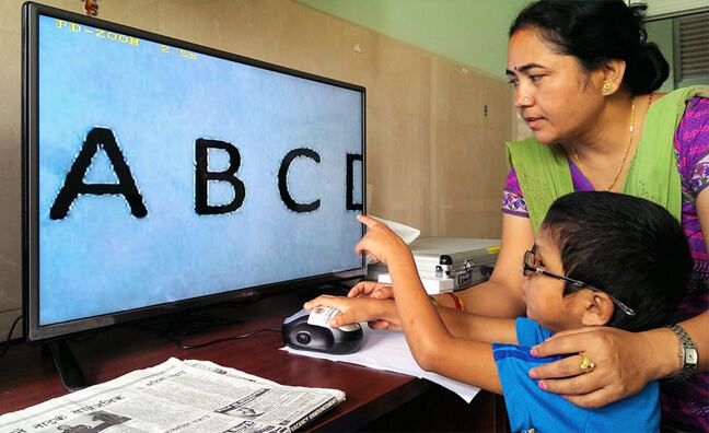 Small boy wearing spectacles is sitting at a desk and pointing at the magnified letters ABCD on a large computer screen whilst a woman operates the computer mouse standing behind him