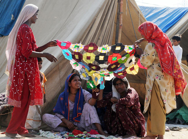 Photograph of Pakistani women making a traditional Sindhi rilley, used as a bed sheet or decor, at a makeshift tent camp in Karachi on October 6, 2010