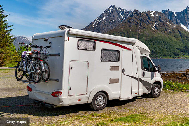 Photograph of campervan parked by a lake - Getty Images
