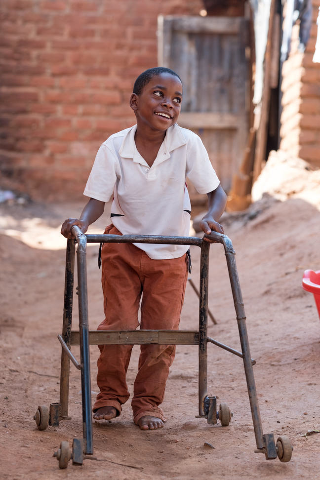 A young boy walking with support from a walking frame