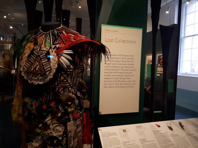 Lost Collections label and display of artwork made up of costume visible with tapa cloth, feathered cloak, collar with nails and neck adornment with lace and coins