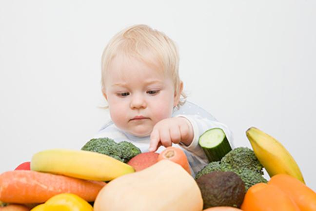 a very young child examining a variety of raw vegetable, decorative only