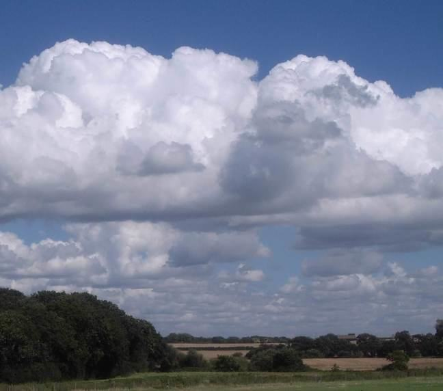 A photograph of some cumulus clouds forming over the countryside