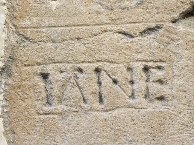 A close up photograph of the word Jane carved into a stone wall