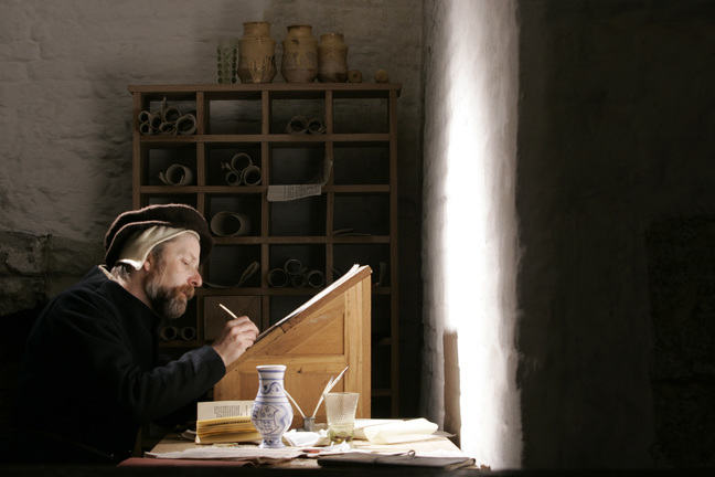 A photograph of a reenactment with a Tudor Clerk of the kitchens, writing at his desk