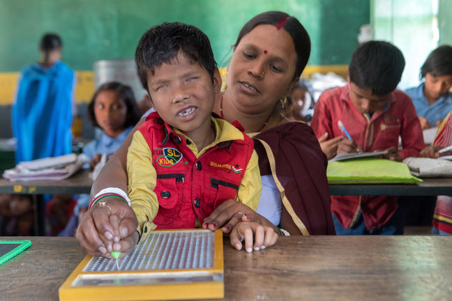 A boy without retina is sitting on the lap of a woman in school. She is helping him read a braille tablet