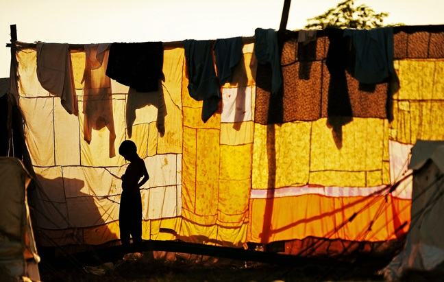 Photograph of a boy silhouetted in front of a washing line at Utmanzai relief camp near Charsadda, northwest Pakistan, on September 24, 2010