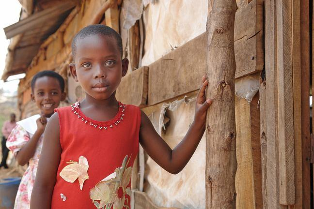 A young girl leans an arm against a wooden building and looks into the camera