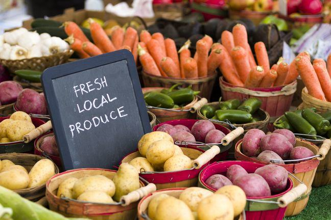 part of a greengrocers stall, with a small blackboard saying 'FRESH LOCAL PRODUCE'